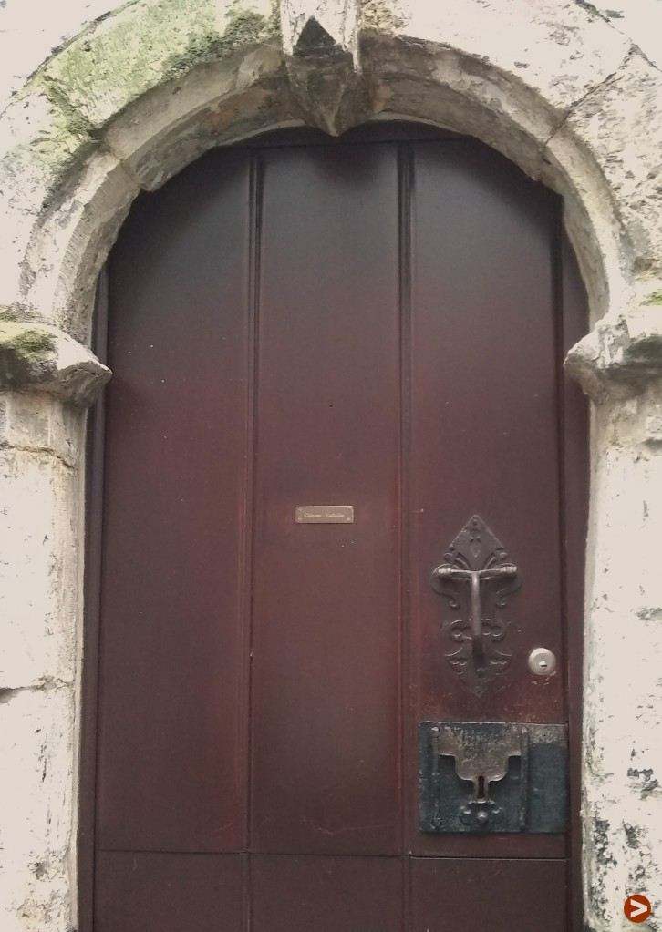 Door in a 16th century stone arch, and with a lock that has two metal strips leading to a keyhole
